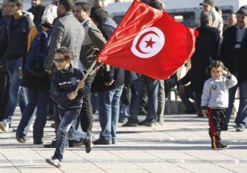 "<strong>December 2013:</strong> A Tunisian boy waves a flag as he runs at a rally in Tunis, marking the third anniversary of Tunisia's revolution. A prominent member of the group that's credited with averting civil war in the country says the group acted ""to give hope to young people."""