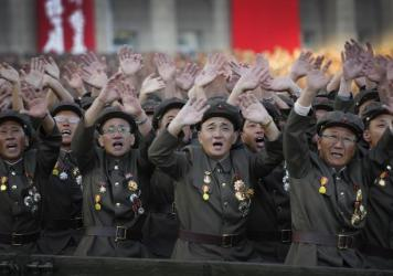 North Korean military soldiers wave as they parade past North Korean leader Kim Jong Un on Saturday.