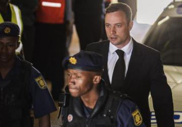 South African athlete Oscar Pistorius (right) is escorted to a police vehicle following his sentencing at the High Court in Pretoria, South Africa, on Oct. 21, 2014.