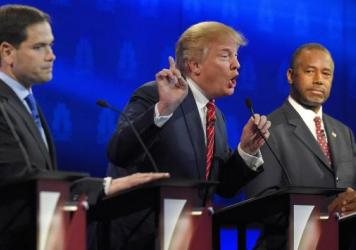 Donald Trump, center, makes a point as Marco Rubio, left, and Ben Carson look on during the CNBC Republican presidential debate at the University of Colorado, Boulder.