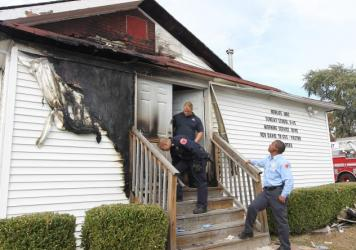 Members of the St. Louis Fire Department inspect the outside of the New Life Missionary Baptist Church in north St. Louis on Oct. 20, three days after a fire was intentionally set. On Oct. 30, a man was charged in connection with setting the fire.