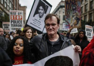 """Director Quentin Tarantino attends a march to denounce police brutality in New York City on Oct. 24. At the rally, Tarantino said, """"I have to call the murdered the murdered, and I have to call the murderers the murderers"""" — drawing considerable backlas"""