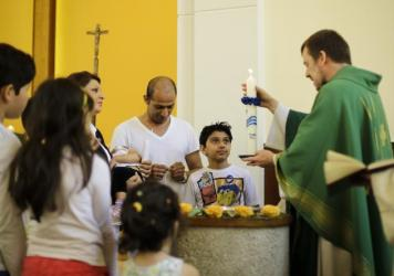 In Berlin, Rev. Gottfried Martens lights a candle during a service to baptize Iranians in the Trinity Church. Iranian and Afghan converts make up most of the 900-member congregation.