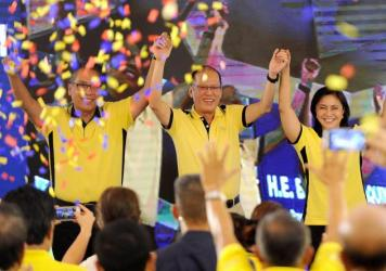 President Benigno Aquino, center, appears with his party's next presidential and vice presidential candidates, Manuel Roxas, left, and Leni Robredo. Aquino is the son of former President Corazon Aquino.