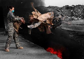 A U.S. airman tosses uniforms into a burn pit at Balad Air Base, Iraq, in 2008. The military destroyed uniforms, equipment and other materials in huge burn pits in Iraq and Afghanistan. Some veterans say those pits are responsible for respiratory problems they are now experiencing.