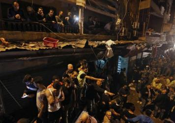People gather near the site of a twin suicide attack Thursday in Burj al-Barajneh, southern Beirut, Lebanon. The self-proclaimed Islamic State has claimed responsibility for the attack.