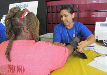 Diana Venegas, a nursing student at Samuel Merritt University, in Oakland, Calif., takes a patient's blood pressure at a recent health fair at Allen Temple Baptist Church.