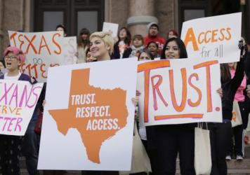Abortion rights activists hold signs during a rally on the steps of the Texas Capitol in June.