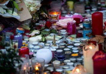 An Eiffel Tower figure sits among candles in memory of the victims of Friday's attacks near the Bataclan concert hall in Paris.