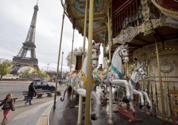 A child walks past an empty merry-go-round near the Eiffel Tower in Paris on Monday.