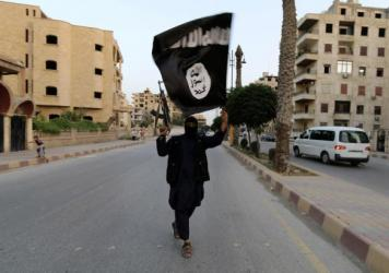 An Islamic State supporter waves the group's flag in its de facto capital of Raqqa, Syria, in June 2014. The group had focused on building its caliphate, or Islamic empire, in the Middle East. But it has claimed three major attacks recently, leading to a reassessment of the group and its goals.