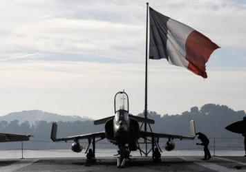 A French sailor checks a Super-Etendard fighter jet on the deck of France's nuclear-powered aircraft carrier Charles de Gaulle before it leaves its home port of Toulon on Wednesday. France has deployed its aircraft carrier in the eastern Mediterranean to