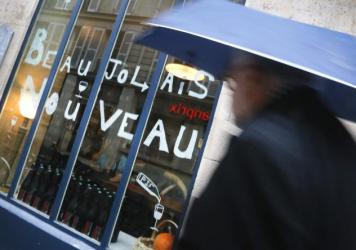 A man walks past a bar advertising Beaujolais Nouveau Day in Paris. Many bars and restaurants were sparsely crowded on a day that normally is a time to celebrate.