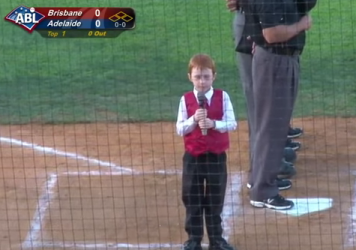A 7-year-old boy sings the Australian national anthem before a baseball game.