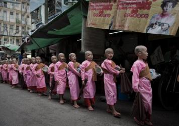 On the road to Buddhist monkhood, young novices chant mantras and collect alms on a street in Yangon, Myanmar.