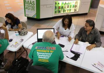 Martha Lucia (from left), Bienvendida Barreno and Jorge Baquero discuss health insurance options with agents from Sunshine Life and Health Advisors at a Miami mall last month.
