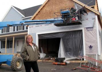 De Desharnais, a homebuilder and real estate agent in Nashua, N.H., stands in front of a house her company is constructing. She says her company had 32 employees at the height of the housing boom, and now only has six despite the industry's gradual recov