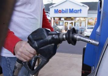 Plummeting energy prices have hit the junk bond market hard, making investors worry that weaker oil and gas companies won't be able to pay back money they've borrowed. Above, a customer pumps gasoline in Pembroke, Mass.