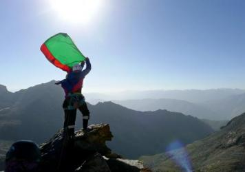 Two young Afghan women, Shopirai Otmonkhel and Zahra Karimi Nooristani, hold the Afghan flag on an unnamed peak in Panjshir. They were among 13 Afghan girls and young women who took part in a 16-day climbing expedition in northeast Afghanistan.