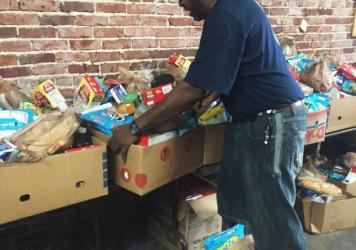 Siegfried Powell moves boxes of food at a food pantry set up in the United Steelworkers Union in Birmingham, Ala. He was laid off from his job at Fairfield Works mill after working there for 26 years.