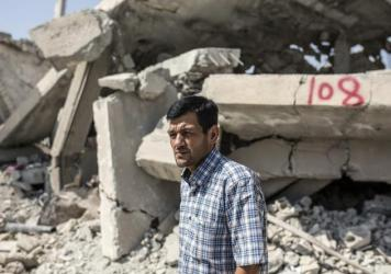 Abdullah Kurdi, father of 3-year-old Aylan Kurdi, who drowned off Turkey, stands in front of his neighbor's house on Sept. 6 in Kobani, Syria.