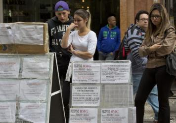 People pause to look at job postings in downtown Sao Paulo, Brazil, last August. The country was especially hard-hit by the slowdown in commodity prices in 2015.
