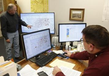 Charles Lord (left), senior hydrologist, explains the mapping procedure used by the Corporation Commission to chart fault lines, earthquakes and disposal wells, as Jim Marlatt, oil and gas specialist, looks on from his desk in Oklahoma City on Nov. 30. S