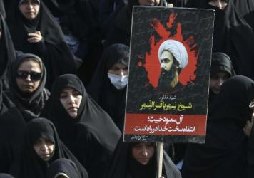 An Iranian woman in Tehran holds up a poster showing Sheikh Nimr al-Nimr, a prominent opposition Saudi Shiite cleric who was executed in Saudi Arabia on Jan. 2.