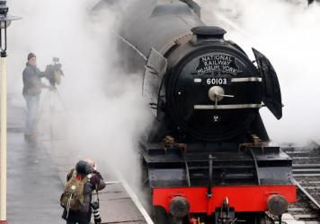 The Flying Scotsman pulls carriages on a test run in Bury on Friday, the first time in 10 years. The train's decade-long restoration is just completed — but it has yet to be repainted in its signature green color.