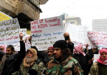 On Jan. 5, demonstrators in Maaret al-Numan, in the Idlib province of Syria, hold banners during a protest for civilians who starved to death in Madaya. Aid is expected to reach Madaya Monday. On Saturday, Maaret al-Numan, the city shown here, was hit by