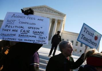 People for and against unions hold up signs Monday in front of the U.S. Supreme Court building in Washington. The court was hearing arguments in <em>Friedrichs v. California Teachers Association.</em> Justices will decide whether California and other sta