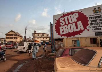 "A corpse has tested positive for the Ebola virus in Sierra Leone, a day after world health officials declared West Africa free of the disease. On Friday, people pass a banner reading ""STOP EBOLA"" — part of Sierra Leone's health campaign — in the city of Freetown."