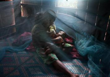 Yonta, 6, rests with her sister Montra, 3, and brother Leakhena, 4 months, under a mosquito bed net during monsoon season in July 2010, in Pailin province, Cambodia.
