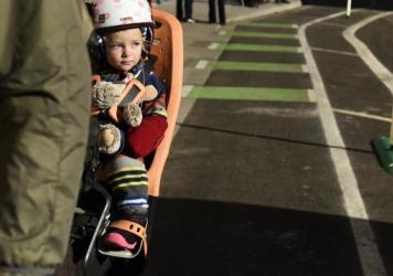Maxien Parrish, 18 months old, is one of the youngest people to enjoy a new bike lane in Denver last month. Two avid bicyclists argue that better bike infrastructure allows slower cycling and a wider age-range of riders.