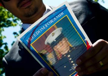 A man reads a flyer with a photo of U.S. Marine veteran Amir Hekmati on May 19, 2014, during a vigil held in Lafayette Park across from the White House in Washington, D.C. The vigil was held on the 1,000th day of Amir's imprisonment in Iran. Hekmati was set to be released Saturday as part of a prisoner exchange.