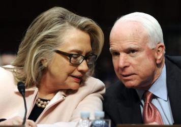Hillary Clinton confers with Republican Sen. John McCain in 2013.