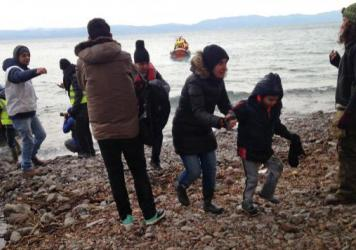 Volunteers help Afghan and Syrian migrants off a rubber boat on a rocky beach in northern Lesbos, Greece.