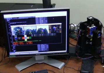 An image from a YouTube video shows a robot (right) that uses a computer to quickly analyze and solve a Rubik's Cube.