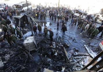 Syrian pro-government forces and residents gather at the site of suicide bombings in the area of a revered Shiite shrine on the outskirts of Damascus, on Sunday. The Islamic State group claimed responsibility for bombings that killed at least 45 people.