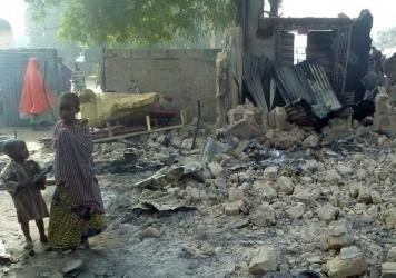 Children stand near the rubble of a burnt house after Boko Haram attacks at Dalori, in northeastern Nigeria, on Sunday.