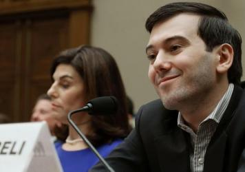 Martin Shkreli, former CEO of Turing Pharmaceuticals, smiles beside Nancy Retzlaff, Turing's chief commercial officer, during a House Oversight and Government Reform Committee hearing on Capitol Hill on Thursday.