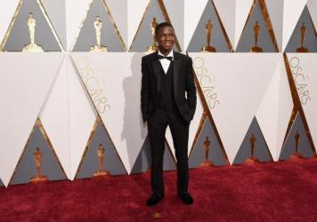 Actor Abraham Attah attends the Academy Awards in a tux and Toms footwear.