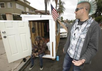 Los Angeles resident Elvis Summers poses with his tiny house on wheels he built. Summers never thought more than 5.6 million people would watch a YouTube video of him constructing the 8-foot-long house, which is small enough to fit in a parking space.