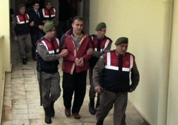 Turkish paramilitary police officers escort Syrian smugglers Muwafaka Alabash (front) and Asem Alfrhad (rear) for their trial in Bodrum, Turkey.