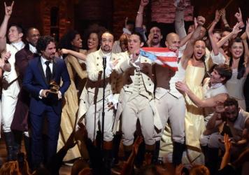 Music director Alex Lacamoire and actor/composer Lin-Manuel Miranda celebrate onstage during a <em>Hamilton</em> performance for the Grammy Awards at Richard Rodgers Theater in New York on Feb. 15.
