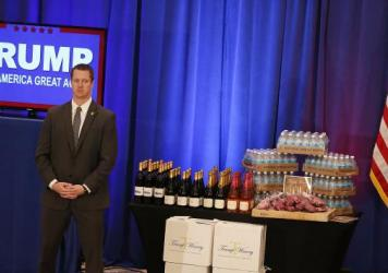 A security agent stands near a display of Trump-branded products that Republican presidential candidate Donald Trump had for guests, including meat, wine and water, before Trump's Tuesday night press conference after the Michigan and Mississippi primarie