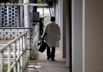 A doctor walks through a hallway at the Centro Medico trauma center in San Juan, Puerto Rico, in 2013. A medical exodus has been taking place for a decade in the Caribbean territory as doctors and nurses flee for the U.S. mainland, seeking higher salarie