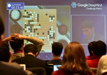 Journalists watch a big screen showing live footage of the third game of the Google DeepMind Challenge Match between Lee Sedol, one of the greatest modern players of the ancient board game Go, and the Google-developed supercomputer AlphaGo at a hotel in Seoul on Saturday. AlphaGo won, clinching its victory in the best-of-5 match.