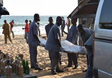 """Employees load a body into a van after heavily-armed gunmen opened fire in the Ivory Coast resort town of Grand-Bassam, leaving bodies strewn on the beach, killing more than a dozen people. The assailants, who were """"heavily armed and wearing balaclavas,"""