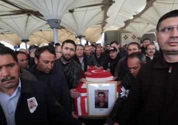 Family members and friends carry the Turkish flag-draped coffin of Murat Gul, 20, a security agent killed in Sunday's explosion, during his funeral procession in Ankara, Turkey.